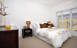 Det lyxiga sovrummet av ett modernt hus inklusive vit täcker med ett H Arkivbild