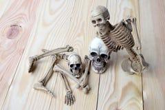 Det mänskliga skalle- och människaskelettet sörjer på träbakgrund Arkivfoto