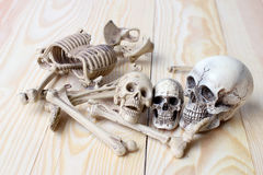 Det mänskliga skalle- och människaskelettet sörjer på träbakgrund Royaltyfri Foto