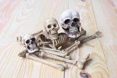 Det mänskliga skalle- och människaskelettet sörjer på träbakgrund Royaltyfria Bilder