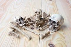 Det mänskliga skalle- och människaskelettet sörjer på träbakgrund Arkivbild