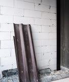 Det mörka tegelplattataket lägger på tegelstenväggen arkivbild