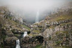 det majestätiska icelandic landskapet med vattenfallet vaggar på i dimma, arkivbilder