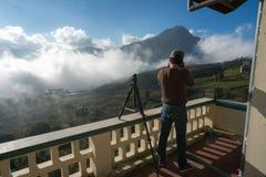 Det manliga turist- tagande fotoet av berglandskapet med låg vit fördunklar under briljant himmel Idéer för lopp och turism royaltyfri bild