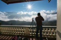 Det manliga turist- tagande fotoet av berglandskapet med låg vit fördunklar under briljant himmel Idéer för lopp och turism royaltyfria foton