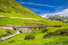Det Matterhorn - Gotthard - Bahn drevet på viaduktbron nära Andermatt i schweiziska fjällängar Arkivfoton