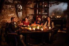 Det medeltida folket äter och dricker i forntida slottkökinre Royaltyfri Bild
