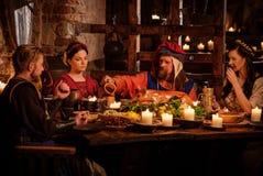 Det medeltida folket äter och dricker i forntida slottkökinre Royaltyfri Foto