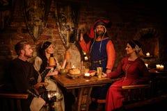 Det medeltida folket äter och dricker i forntida slottkrog Royaltyfri Fotografi