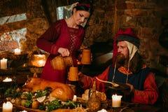 Det medeltida folket äter och dricker i slottkrog Royaltyfri Foto
