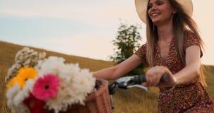 Det mellersta planet är blondinen i hatten rider en cykel med blommor och leenden arkivfilmer