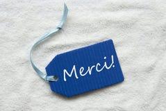 Det Merci medlet tackar dig på bakgrund för blåttetikettsand Royaltyfria Foton