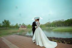 Det merried glamourbarnet kopplar ihop att kyssa under paraplyet Royaltyfri Fotografi