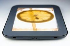Tablethandlag vadderar datoren med citronen Arkivfoto