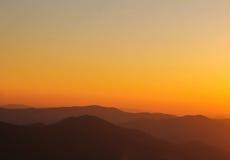 Det minsta berget formar på horisonten under solnedgång Royaltyfri Bild