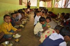 Det mitt- dagmålprogrammet, en Indiens regeringinsats, kör i en grundskola för barn mellan 5 och 11 år Elever tar deras mål royaltyfri bild