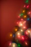 Det mång- färgjulträdet tänder bokeh som bubblor på en röd bakgrund Arkivfoton