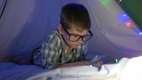 Det mobila barnet, pys i glasögon spelar på smartphonelögnerna i vigvam med en girland arkivfilmer