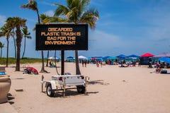 Det mobila tecknet på stranden som säger, kasserat plast- avfall, är dåligt för miljön royaltyfria bilder
