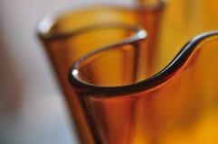 Det moderna Amber Glass Art Vase Abstract lynnet buktar serien Backgrou royaltyfri fotografi