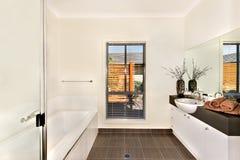 Det moderna badrummet med ett vatten badar och badningområde som är motsatt till th royaltyfri foto