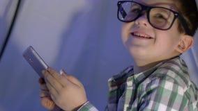 Det moderna barnet i glasögon håller ögonen på videoen in i smartphonen i vigvamnärbild lager videofilmer