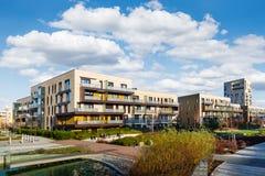 Det moderna huset med lägenheter som lokaliseras i gräsplanen, parkerar Fotografering för Bildbyråer
