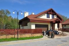 Det moderna huset med loften, garaget och fäktning med massor av avskräde för byggnadskonstruktion i gabage hänger löst arkivfoton