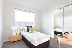 Det moderna sovrummet med en enkel säng och en vit täcker nära en spegel Arkivbild