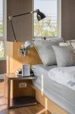 Det moderna sovrummet med träsäng och tabellen sid Royaltyfri Bild