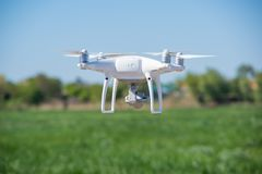 Det moderna surret, quadrocopter är i luften mot bakgrunden av himlen och gräset Fotografering för Bildbyråer