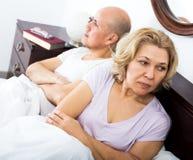 Det mogna paret grälar i säng Arkivbild