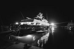 Det monokromma fotoet av den lyxiga privata yachten förtöjde på pir på ni Arkivbild