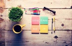 Det Motivational citationstecknet på färgrika klibbiga anmärkningar som är olika stelnar pennor och koppen kaffe Arkivfoton