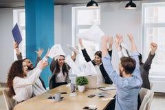 Det multietniska olika lyckliga laget firar upp papper f?r projektframg?ngkastet tillsammans F royaltyfri bild