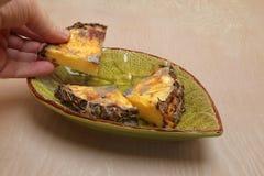 Det murkna stycket av ananas rymde i en hand Arkivfoton