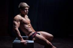 Det muskulösa sexiga barnet blöter naket idrottsman nensammanträde Arkivfoton