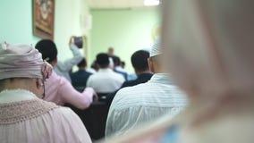 Det muslimska folket som sitter på fåtöljer på det islamiskt mass, samlar arkivfilmer