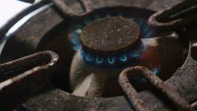 Det nära övre detaljskottet av den gamla rostiga cirkeln för kökugnen kopplade på brand med ljusare flammabränning i farlig gasen arkivfilmer