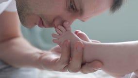 Det nära övre skottet av fadern som kysser fot av, behandla som ett barn stock video