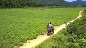 Det nära baksiktsparet rider sparkcykeln på jordnötfält lager videofilmer