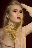 Det nätta barnet modellerar med långa blont hår och modeller av guld- Arkivfoto