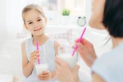 Det nätta gulliga småbarnet dricker den läckra coctailen, har angenämt fotografering för bildbyråer