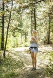 Det nätta kvinnaanseendet i sommarträt och att kasta sörjer kottar royaltyfri fotografi