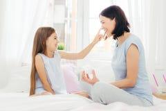 Det nätta lilla kvinnliga barnet har gyckel samman med hennes moder, applicerar skönhetkräm på hennes näsa, sitter tillsammans på fotografering för bildbyråer