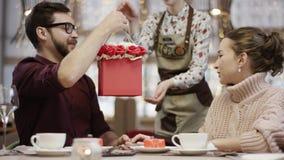 Det nätta paret som sitter i restaurang vid tabellen, när uppassaren kommer med en ask mycket av blommor och mannen, ger den till stock video