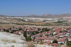 Det naturliga landskapet och husen av den Cappadocia regionen Arkivfoton