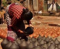 Det nepalesiska folket är forma och torka upp keramikkrukor i krukmakerifyrkant royaltyfri foto