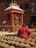 Det nepalesiska folket är forma och torka upp keramikkrukor i krukmakerifyrkant royaltyfri bild