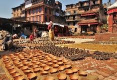 Det nepalesiska folket är forma och torka upp keramikkrukor i krukmakerifyrkant arkivfoton